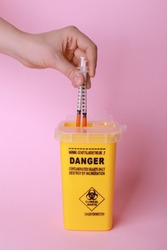Woman throwing used syringes into sharps container  on pink background, closeup