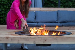 woman throws logs on fire pit in the garden on a summer day close-up