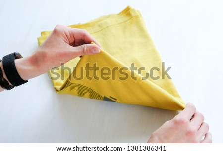 Woman tidy folds male t-shirt on a white background #1381386341