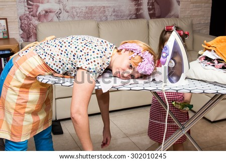 Woman tired ironed clothes and lay down on the ironing board