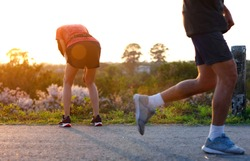 woman tired on running jogging exercise by hand resting on the knees, workout running of woman unfit and tired often