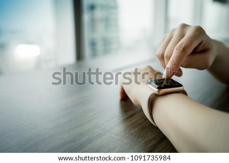 woman touch on the screen of the smartwatch on your hand, wood table at the room, copy space picture.