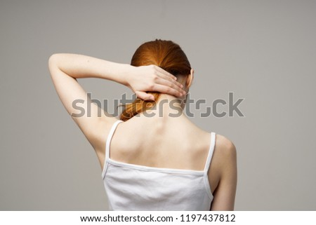 woman touches her neck on a gray background back view                             #1197437812