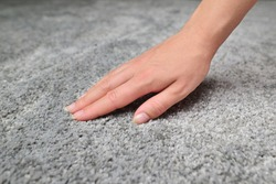 Woman touching grey carpet, close up. Close up of hand touching soft carpet. Gentle and fluffy carpet between fingers.