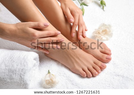 Woman touching her smooth feet on white towel, closeup. Spa treatment