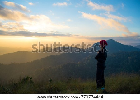 Woman tourism hiking vacation and travel. Tourist woman in camping site standing and enjoying mountains landscape view of sunset, sunrise at winter mountain in Chiangmai, Thailand. #779774464