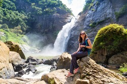 Woman tourist and Dunhinda waterfall in a sunny day in Sri Lanka