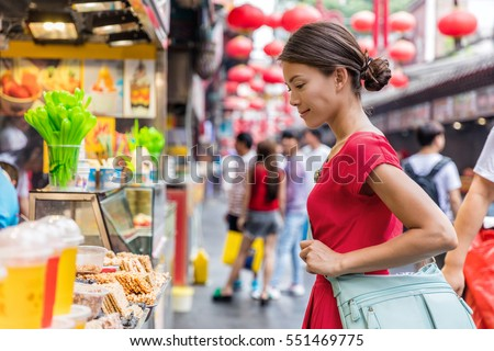 Woman tourist at chinese market Wangfujing, food street on Asia travel. Traditional Beijing snacks at outdoor market place. Asian woman looking at restaurant or outside store.
