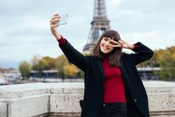 Woman tourist at Eiffel Tower smiling and making travel selfie. Beautiful European girl enjoying vacation in Paris, France