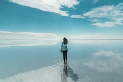 Woman tourist & beautiful mirror reflection on blue sky and cloud on Bolivia's Salt Flats. Shot in Salar de Uyuni salt flat. Water reflection of clouds and empty space. Holiday, vacation travel scene
