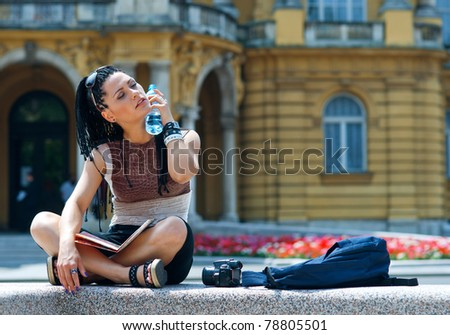 woman tourist cooling herself with water bottle