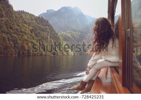 Woman tourist going on boat in Konigssee lake, Berchtesgaden, Germany. Young brunette traveler with blowing long hair in warm cozy clothes style enjoying and relax.