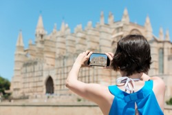 Woman tourist in Mallorca taking photographs of landmark buildings while enjoying the adventure of a a summer vacation in Europe, view from behind
