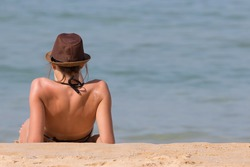 Woman Tourist in Swimsuit and Hat Lying for Sunbathe and Relax on Nai Yang Sea Beach of Phuket, Thailand Set as Copy Space for Text.
