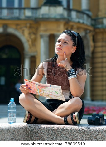 woman tourist looking at map and thinking in old city site