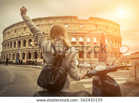 Woman tourist near the Coliseum in Rome under sunlight and blue sky. Famous popular touristic place in the world. #562435159