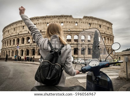 Woman tourist near the Coliseum in Rome under sunlight and blue sky. Famous popular touristic place in the world. #596056967