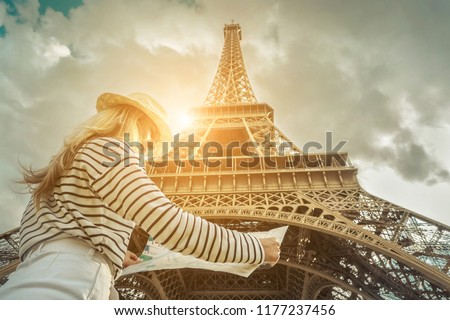 Woman tourist near the Eiffel Tower in Paris under sunlight and blue sky. Famous popular touristic place in the world. #1177237456