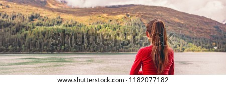 Woman tourist on Autumn travel holiday relaxing at fall foliage forest background in cozy woods cabin or cruise balcony outdoor resort. Banner panorama.