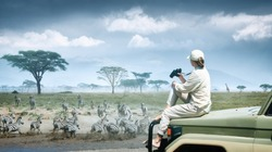 Woman tourist on safari in Africa, traveling by car in Kenya and Tanzania, watching zebras and antelopes in the savannah. Adventure and wildlife exploration in Africa. Serengeti National Park.