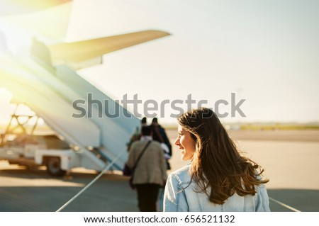 Woman tourist passager getting in to airplane at airport, walking from the terminal to the plane.