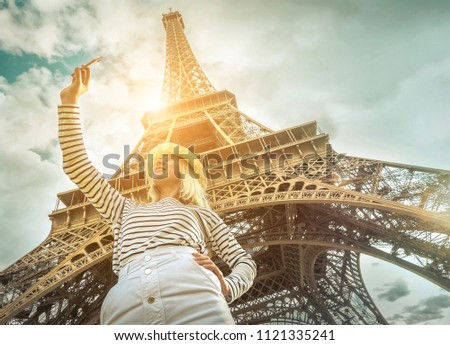 Woman tourist selfie near the Eiffel Tower in Paris under sunlight and blue sky. Famous popular touristic place in the world. #1121335241