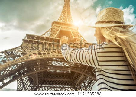 Woman tourist selfie near the Eiffel Tower in Paris under sunlight and blue sky. Famous popular touristic place in the world. #1121335586