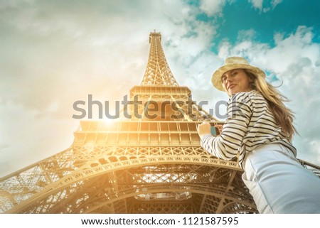 Woman tourist selfie near the Eiffel Tower in Paris under sunlight and blue sky. Famous popular touristic place in the world. #1121587595