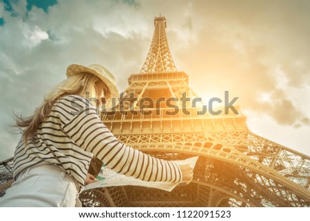 Woman tourist selfie near the Eiffel Tower in Paris under sunlight and blue sky. Famous popular touristic place in the world. #1122091523