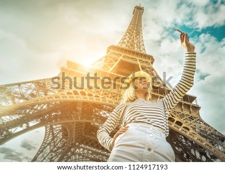 Woman tourist selfie near the Eiffel Tower in Paris under sunlight and blue sky. Famous popular touristic place in the world. #1124917193