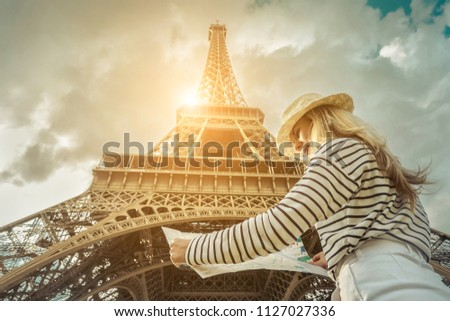 Woman tourist selfie near the Eiffel Tower in Paris under sunlight and blue sky. Famous popular touristic place in the world. #1127027336