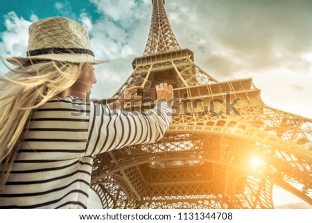 Woman tourist selfie near the Eiffel Tower in Paris under sunlight and blue sky. Famous popular touristic place in the world. #1131344708