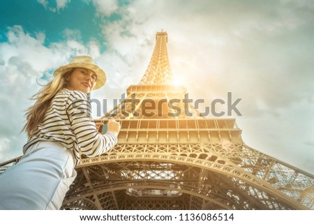 Woman tourist selfie near the Eiffel Tower in Paris under sunlight and blue sky. Famous popular touristic place in the world. #1136086514
