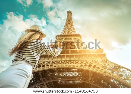 Woman tourist selfie near the Eiffel Tower in Paris under sunlight and blue sky. Famous popular touristic place in the world. #1140164753