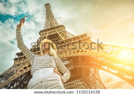 Woman tourist selfie near the Eiffel Tower in Paris under sunlight and blue sky. Famous popular touristic place in the world. #1150516538