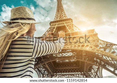Woman tourist selfie near the Eiffel Tower in Paris under sunlight and blue sky. Famous popular touristic place in the world. #1159142854
