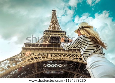 Woman tourist selfie near the Eiffel Tower in Paris under sunlight and blue sky. Famous popular touristic place in the world. #1184379280
