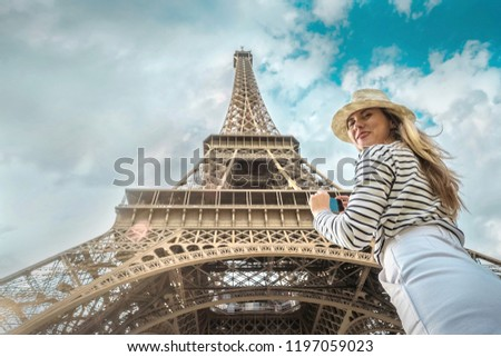 Woman tourist selfie near the Eiffel Tower in Paris under sunlight and blue sky. Famous popular touristic place in the world. #1197059023