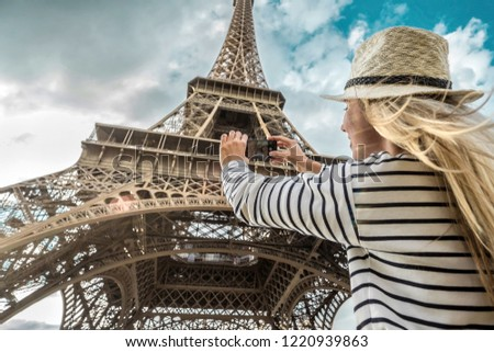 Woman tourist selfie near the Eiffel Tower in Paris under sunlight and blue sky. Famous popular touristic place in the world. #1220939863