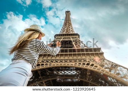 Woman tourist selfie near the Eiffel Tower in Paris under sunlight and blue sky. Famous popular touristic place in the world. #1223920645