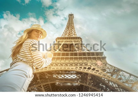 Woman tourist selfie near the Eiffel Tower in Paris under sunlight and blue sky. Famous popular touristic place in the world. #1246945414