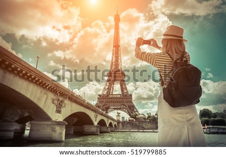 Woman tourist selfie near the Eiffel tower in Paris under sunlight and blue sky. Famous popular touristic place in the world. #519799885