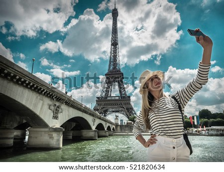 Woman tourist selfie near the Eiffel tower in Paris under sunlight and blue sky. Famous popular touristic place in the world. - Shutterstock ID 521820634