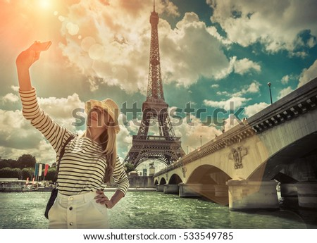 Woman tourist selfie near the Eiffel tower in Paris under sunlight and blue sky. Famous popular touristic place in the world. - Shutterstock ID 533549785