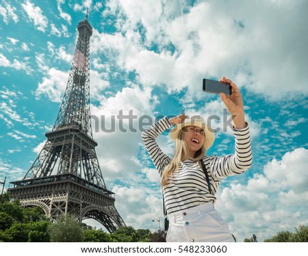 Woman tourist selfie near the Eiffel tower in Paris under sunlight and blue sky. Famous popular touristic place in the world. #548233060