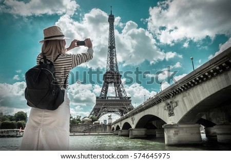 Woman tourist selfie near the Eiffel tower in Paris under sunlight and blue sky. Famous popular touristic place in the world. - Shutterstock ID 574645975