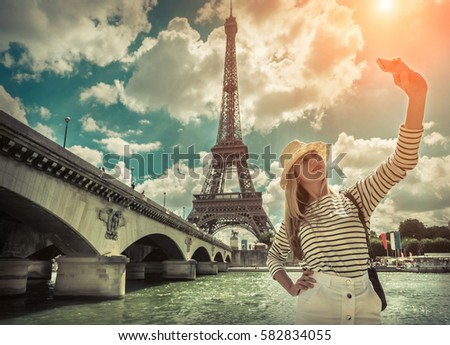 Woman tourist selfie near the Eiffel tower in Paris under sunlight and blue sky. Famous popular touristic place in the world. - Shutterstock ID 582834055