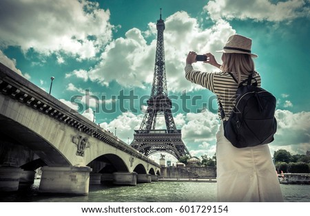 Woman tourist selfie near the Eiffel tower in Paris under sunlight and blue sky. Famous popular touristic place in the world. - Shutterstock ID 601729154