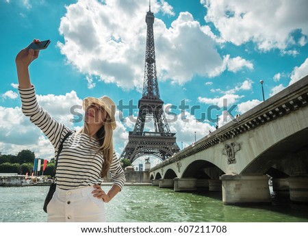 Woman tourist selfie near the Eiffel tower in Paris under sunlight and blue sky. Famous popular touristic place in the world. - Shutterstock ID 607211708