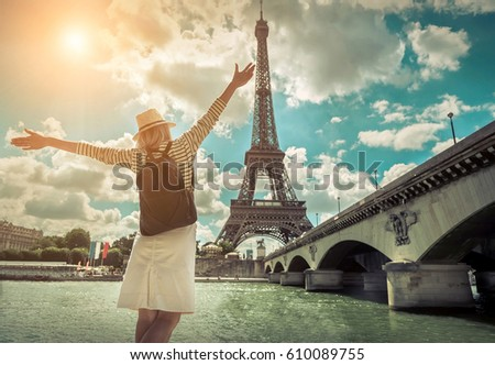 Woman tourist selfie near the Eiffel tower in Paris under sunlight and blue sky. Famous popular touristic place in the world. - Shutterstock ID 610089755